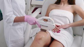 Beautician doctor doing elos hair removal depilation on attractive young woman legs in beuty salon. Hardware aesthetic. Cosmetology. Laser epilation on feet in stock video footage