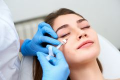 Doctor in medical gloves with syringe injects botulinum under eyes for rejuvenating wrinkle treatment. Filler injection. Beautician doctor in medical gloves with stock photography