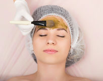 Beautician does cosmetic mask on the patient's Royalty Free Stock Photos