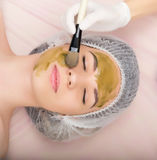 Beautician does cosmetic mask on the patient's Stock Image