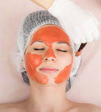Beautician does cosmetic mask on the patient's Royalty Free Stock Image