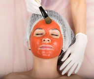 Beautician does cosmetic mask on the patient's Stock Photos