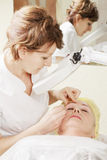 Beautician does eyebrows tweezing procedure Royalty Free Stock Images
