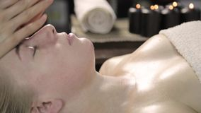 Beautician does facial massage for beautiful woman in spa saloon.