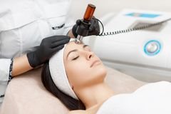 Cosmetology specialist doing radio frequency lifting in beauty salon. Beautician doing anti-wrinkle facial treatment for problematic skin, with help of beauty Stock Image