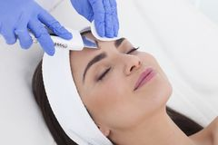 Beautiful woman is having a facial treatment in spa. Beautician is doing a facial treatment to her patient Royalty Free Stock Photo
