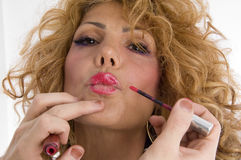 Beautician doing lip make up of woman Stock Photos