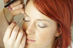 Beautician is doing make-up to red-haired girl Royalty Free Stock Image