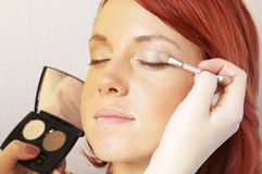 Beautician is doing make-up to red-haired girl Stock Photography