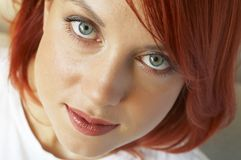 Beautician is doing make-up to red-haired girl stock photos