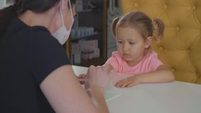Beautician doing manicure for little baby girl at beauty spa salon. . stock video footage
