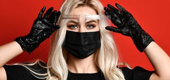 Beautician doing tattooing eyebrow permanent make-up for eyebrows in black gloves and mask on red background stock photography