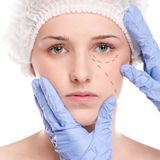 Beautician draw correction lines on woman face Stock Photography