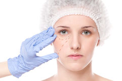 Beautician draw correction lines on woman face Royalty Free Stock Photos