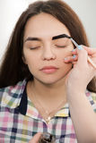 Beautician dying eyebrows with henna. Beautician is coloring with henna brow of young girl. Unrecognizable woman hand dying model`s eyebrows Royalty Free Stock Photos