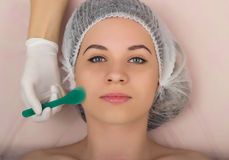 Beautician examining the face of a young female client at spa salon. beautician does cosmetic mask on the patient's face Stock Image