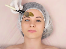 Beautician examining the face of a young female client at spa salon. beautician does cosmetic mask on the patient's face Royalty Free Stock Image