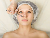 Beautician examining the face of a young female client at spa salon. face cleaning, Una cuchara. Professional Royalty Free Stock Photography