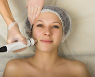 Beautician examining the face of a young female client at spa salon. getting rf-lifting in a beauty salon. Professional Royalty Free Stock Photo