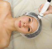 Beautician examining the face of a young female client at spa salon. getting rf-lifting in a beauty salon. Professional Stock Photo