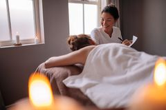 Female massage therapist talking to woman at wellness center. Beautician examining female client before spa treatment and making notes for the therapy. Female stock image