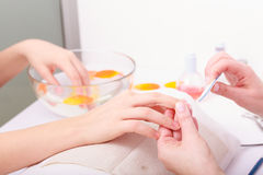Beautician with file filing nails female client. Woman spa beauty salon Stock Photography
