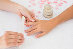 Beautician filing female client's nails at spa beauty salon Royalty Free Stock Photo