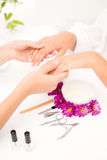 Beautician filing female clients nails at spa beauty salon. Close up of beautician filing female clients nails at spa beauty salon Stock Photography