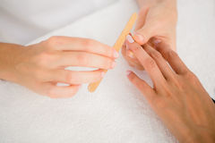 Beautician filing female clients nails at spa beauty salon. Close up of beautician filing female clients nails at spa beauty salon royalty free stock photos