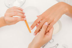 Beautician filing female clients nails at spa beauty salon Stock Images