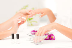 Beautician filing female clients nails at spa beauty salon. Close up of beautician filing female clients nails at spa beauty salon Stock Images