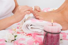 Beautician filing the nails of woman. Close-up Of Beautician Hand Filing The Nails Of Woman In Salon Royalty Free Stock Image