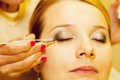 Beautician gives false eyelashes Stock Images