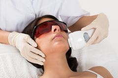 Beautician giving epilation laser treatment. Close-up Of Beautician Giving Epilation Laser Treatment On Woman's Face Royalty Free Stock Photography