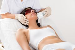 Beautician giving epilation laser treatment. Close-up Of Beautician Giving Epilation Laser Treatment On Woman's Face Royalty Free Stock Images