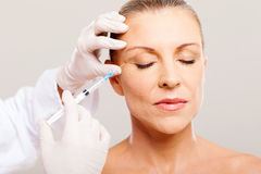 Senior face lifting. Beautician giving face lifting injection on mature woman Royalty Free Stock Image