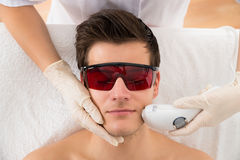 Beautician Giving Laser Epilation Treatment To Man Face. Close-up Of Beautician Giving Laser Epilation Treatment To Young Man Face Stock Image