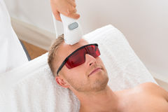 Beautician Giving Laser Epilation Treatment. On Young Man Royalty Free Stock Photo