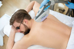 Beautician giving men laser epilation Stock Image