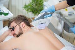 Beautician giving men laser epilation Stock Photos