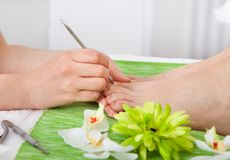 Beautician Giving Pedicure Treatment Royalty Free Stock Photos