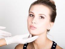 Beautician hand& x27; s egzamininuje piękną młodą żeńską twarz obrazy stock