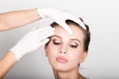 Beautician hand& x27; s egzamininuje piękną młodą żeńską twarz zdjęcia royalty free