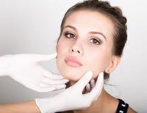 Beautician hand& x27; s egzamininuje piękną młodą żeńską twarz Obrazy Royalty Free
