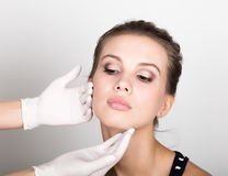 Beautician hand& x27; s egzamininuje piękną młodą żeńską twarz Zdjęcie Royalty Free