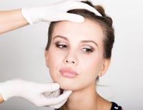 Beautician hand& x27; s egzamininuje piękną młodą żeńską twarz Fotografia Stock