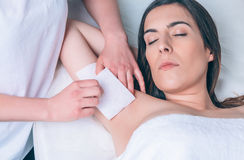 Beautician hands doing depilation in woman armpit. Beautician hands doing depilation armpit to beautiful woman with wax strip in a beauty salon stock photography