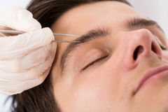 Beautician Hands Plucking Man Eyebrows With Tweezers Royalty Free Stock Photo