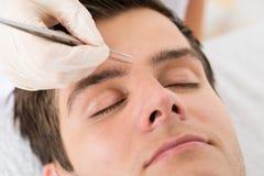 Beautician Hands Plucking Man Eyebrows With Tweezers Stock Images