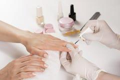 Beautician kobieta stosuje gwoździa połysk w manicure'u studiu na młodej kobiecie obraz stock